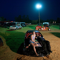USA, Mississippi, Gulfport, Young couple relaxes on hood of stock racing car in pits at South Mississippi Speedway