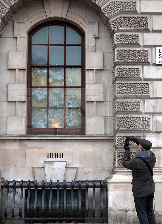 (c) London News Pictures. 10.12.2010. A man takes a picture of broken windows at the Treasury building in Parliament Square. The clean-up operation in Westminster following last night's student demonstration. Picture credit should read: Fuat Akyuz/London News Pictures