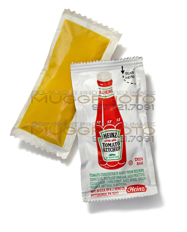 Heinz ketchup and mustard packets on white background