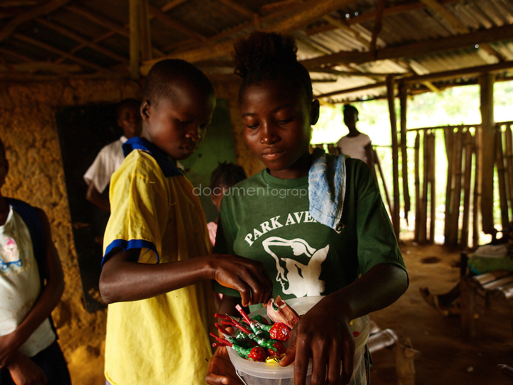 A girl sells sweets to the pupils at J.S. Varfley School, Kingsville #7, Liberia