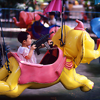 Elephant ride fitted with a machine gun in a city children's park...From China [sur]real © Mark Henley..