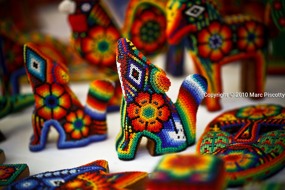 """SHOT 1/29/10 11:30:38 AM - Huichol beadwork for sale in Sayulita, Mexico. The Huichol or Wixáritari are an indigenous ethnic group of western central Mexico, living in the Sierra Madre Occidental range in the Mexican states of Nayarit, Jalisco, Zacatecas, and Durango. They are best known to the larger world as the Huichol, however, they refer to themselves as Wixáritari (""""the people"""") in their native Huichol language. The beaded art is a relatively new innovation and is constructed using glass, plastic or metal beads pressed onto a wooden form covered in beeswax. Common bead art forms include masks, bowls and figurines. Like all Huichol art, the bead work depicts the prominent patterns and symbols featured in the Huichol religion. Sayulita is a small surfing and fishing village about 25 miles north of downtown Puerto Vallarta in the state of Nayarit, Mexico, with a population of approximately 4,000. Known for its consistent river mouth surf break, roving surfers """"discovered"""" Sayulita in the late 60's with the construction of Mexican Highway 200. In recent years, it has become increasingly popular as a holiday and vacation destination, especially with surfing enthusiasts and American and Canadian tourists. (Photo by Marc Piscotty / © 2009)"""