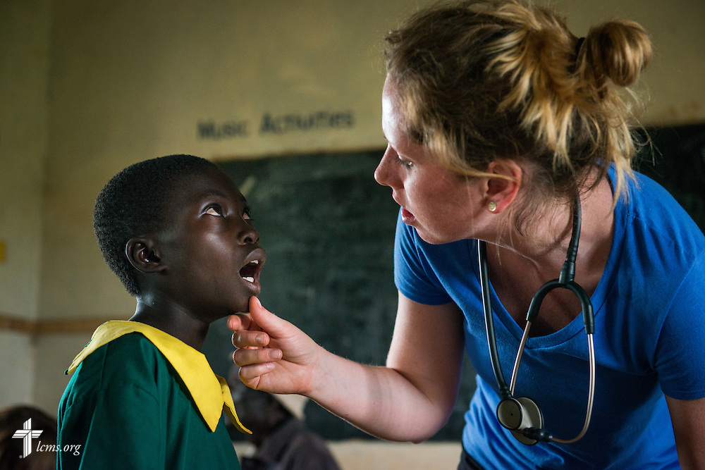 Nurse Casey Peters of Dover, N.H, examines a boy during the Mercy Medical Team clinic Wednesday, June 11, 2014, at the Luanda Doho Primary School in Kakmega County, Kenya. LCMS Communications/Erik M. Lunsford