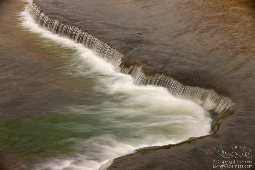 The Genesee River cascades over a drop in the eroded river bed in Letchworth State Park, New York. The area was once submerged under an inland sea, which left deposits that formed sandstone and shale. The Genesee River eroded the river bed, forming small drops like this, as well as the Letchworth Gorge, which is 22 miles (35 km) long and as much as 550 feet (168 meters) deep.