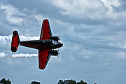 Color image of the distinctive Yournin black and red color scheme on a Twin Beech 18 performing aerobatics