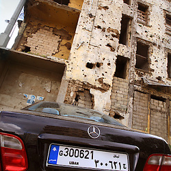 A new Mercedes Benz is seen parked beneath a building yet to be repaired after sustaining damage in the Lebanese civil war in Beirut, Lebanon, March 15, 2006.