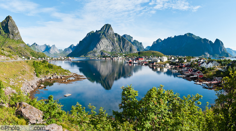 Steep mountains surround the fishing village of Reine on Moskenesøya (the Moskenes Island), in the Lofoten archipelago, Nordland county, Norway. Panorama stitched from 2 overlapping photos.