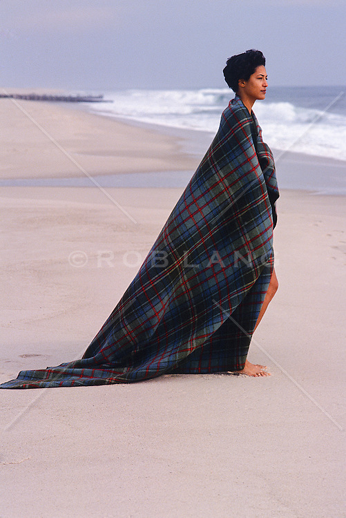 woman in a blanket standing on the beach in Southampton, NY