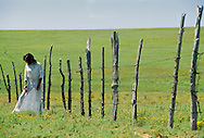 Woman in white dress in contemplation beside fence, <br /> MODEL RELEASED