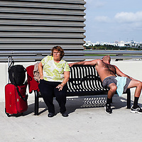 Two people sitting on a sunny bench at a Florida airport.