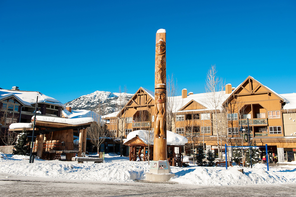 Whistler Village townhouses, totem pole, and stores on a sunny morning in the winter.  Whistler BC, Canada