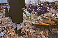 In the wake of the Kobe quake, police officers comb through a demolished apartment house as a woman waits to learn the fate of her husband.  His body was never found.
