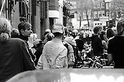 People and riot police mill around in Amsterdam, as nearby a squatters demonstration results in demonstraters being kettled into a small area. The demo marked the first anniversary of the end of squatters rights in the Netherlands