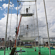 Student Ariel Flavin transitions to a knee hang at Trapeze School New York during the June 4th morning class. The two hour beginner session taught the nine students in attendance the basics of flying trapeze -- including knee hangs and backwards somersaults -- in their facility on the roof of Pier 40...CREDIT: Daniella Zalcman for The Wall Street Journal.SLUG: NYMETROMONEY_Trapeze