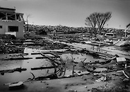 A wall of debris closes in this destroyed neighborhood, still flooded with sea water 6 months later because it has subsided below sea level.  Ishinomaki, Miyagi Prefecture, Japan.