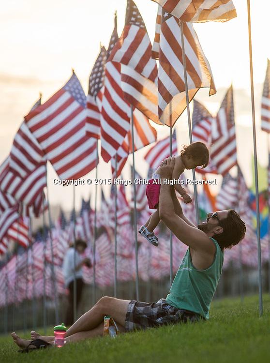 9月10日,在美国加利福尼亚州洛杉矶的马里布,一名父亲高举他的儿子。当天,在美国&ldquo;9&middot;11&rdquo;事件十四周年前夕,佩珀代因大学的学生和教职员工在学校草坪上插起约3000面美国国旗,纪念&ldquo;9&middot;11&rdquo;事件遇难者。新华社发(赵汉荣摄)<br /> A man holds up his son amongst 3,000 US flags are displayed at Pepperdine University to mark the 14th anniversary of the 9/11 terror attack, September 10, 2015 in Los Angeles, California, the United States. (Xinhua/Zhao Hanrong)Photo by Ringo Chiu/PHOTOFORMULA.com)
