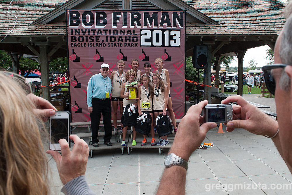 Bob Firman and the Davis girl's team (Front row L to R:  Taylor Cox, Aubrey Argyle, Hannah Albrechtsen. Back row L to R: Aimee Vance, Kenzie Weir, Ashley Tyndall, Josey Hedquist) on the podium stand at the Bob Firman Invitational at Eagle Island State Park in Eagle, Idaho on September 21, 2013. This meet is named in honor of  Mr. Firman who started cross country in Boise. The Davis girls won the 15 team elite race with a team score of 51, followed by Park City (143) and Skyline (145).<br />