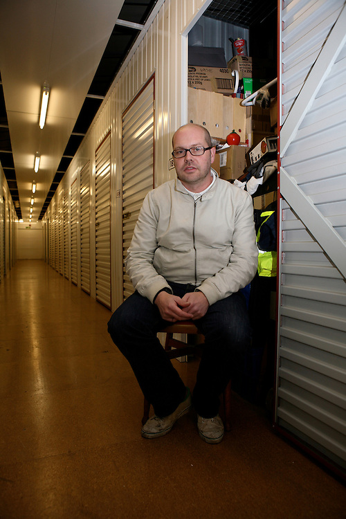 David, 32, student, photographer and graphic designer, in his West London storage. His unit is stuffed with all sorts of things: portfolios, kitchenwares, tools, knick knacks and tiny furniture