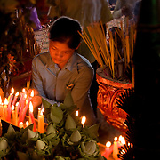 A young woman says a pray in a Buddhist temple in Phnom Penh, Cambodia.