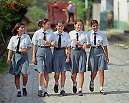 LA REINA, CHALATENANGO, EL SALVADOR: Muchachas de la escuela (school girls) make their way home at the end of the day in La Reina, El Salvador. UNICEF statistics compiled between 2000-2006 indicate that 54% of females in El Salvador reach secondary school enrollment.  (Photo by Robert Falcetti). .