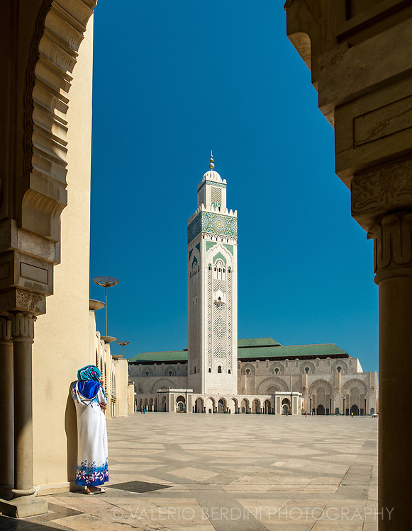 A muslim woman stands next the arcade of Hassan II mosque in Casablanca. The largest mosque in Africa with the tallest minaret in the world.