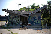 A run down shop covered in graffiti. Since the economic crisis and the collapse of the car industry, around 2/3rd of the population has left Detroit.  This mass exodus has turned Detroit into a ghost town. Detroit, USA, 2011