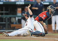 Virginia's Nate Irving (18) scores against Mississippi's Will Allen (30) in the College World Series in Omaha, Neb. on Sunday, June 15, 2014. Virginia won 2-1.