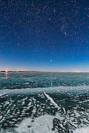 Orion and the Dog Stars (Procyon and Sirius) rising over frozen Lake MacGregor in southern Alberta, on February 2, 2017, on a clear moonlit night, with a 6-day Moon, off frame, lighting the scene. Note the glitter path reflection of Sirius in the ice. <br /> <br /> This is with the Sigma 20mm Art lens and Nikon D750.