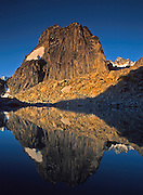 """Sunrise light strikes Snowpatch Spire (10,050 feet) and reflects in a mountain pond (tarn) in Bugaboo Provincial Park, British Columbia, Canada. The Bugaboos are a range in the Purcell Mountains, which are a subrange of the Columbia Mountains, which are west of the Rocky Mountain Trench. (Some USA maps label the """"Percell Mountains"""" where their southern limit protrudes into the states of Idaho and Montana.) The igneous Bugaboo intrusion of 135 million years ago cooled into hard crystalline granite and was scraped into spires by glaciers eroding surrounding rock dating from 600 million to 1 billion years ago. Published in """"Light Travel: Photography on the Go"""" book by Tom Dempsey 2009, 2010."""