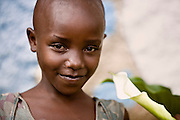 A young Rwandan girl named Monique show's off a calla lily growing outside her home.  Even when people are struggling they respond to beauty.  This is the key to Lily Yeh's work. Using broken communities as her canvas, and people's stories as her pigments, Yeh brings healing, empowerment, and a sense of belonging through the alchemy of community art.
