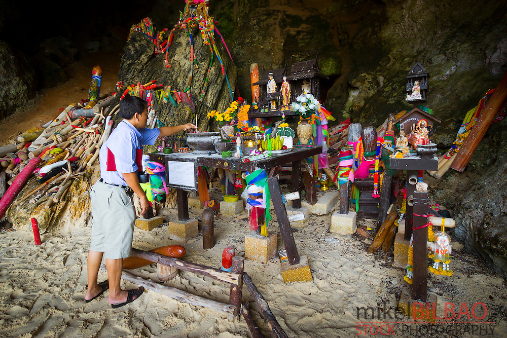 Man in Princess Cave or Tham Phra Nang Nok. Pranang Cave Beach. Railay, Krabi province, Thailand.
