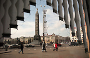 Pedestrians walk near the Victory column in downtown Minsk on April 4, 2006.