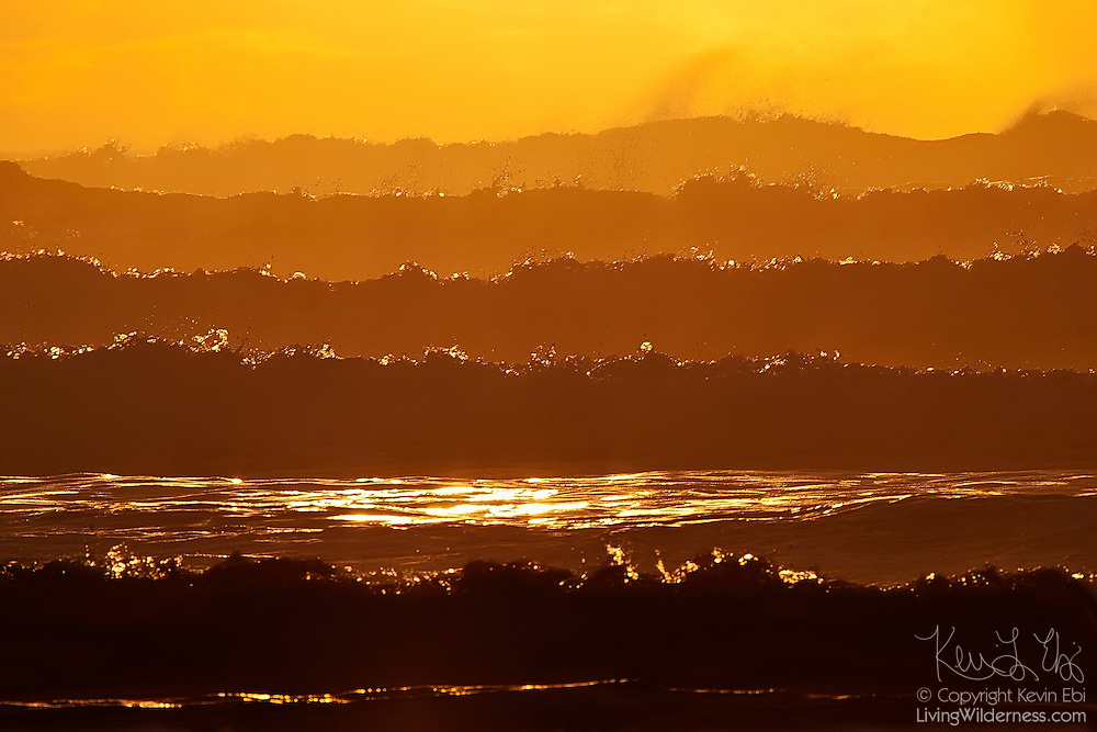 Several layers of Pacific Ocean waves are backlit by the setting sun near Manzanita, Oregon.