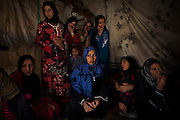 Refugee women from from the besieged neighbourhood of Baba Amr, in Homs city, Syria, sit inside a temporary structure at the Dalhamiye settlement, close to the Syrian border, in the Bekaa Valley, Lebanon. The majority of Syrian refugees in Lebanon live in an urban setting but some temporary camps have been created, usually on land rented by the refugees themselves. There are no official Syrian refugee camps in Lebanon owing to the long history of the Palestinian camps in the country.