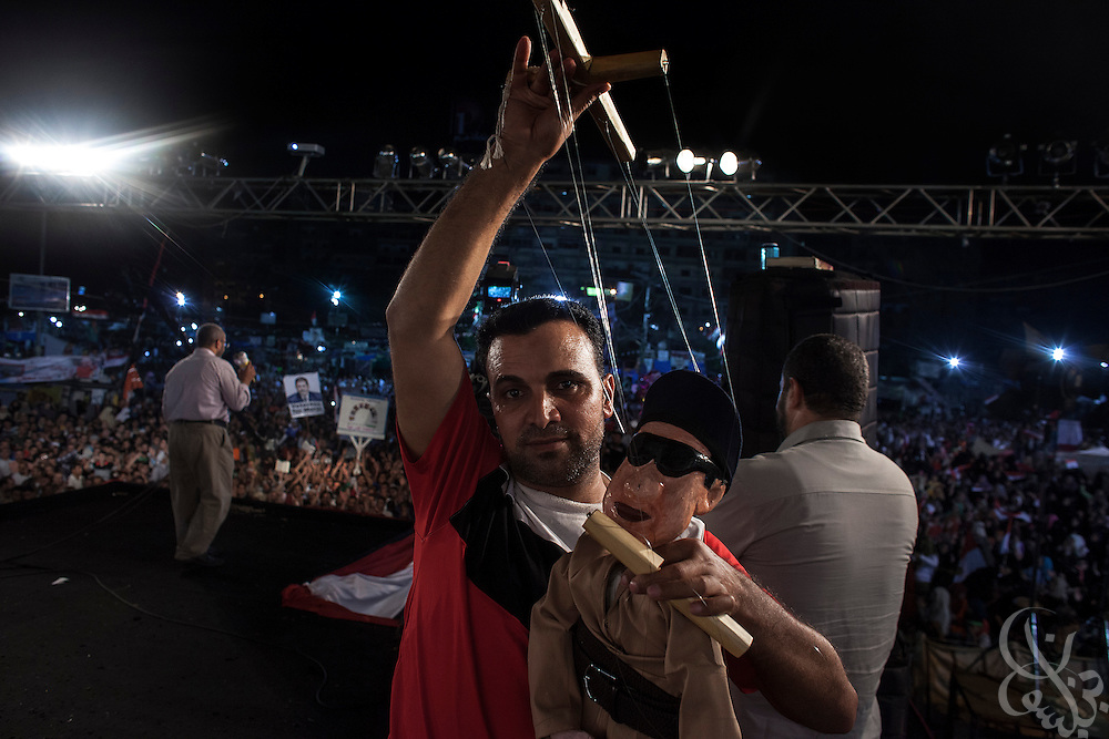 An Egyptian puppeteer holds a marionette likeness of Egyptian Defense Minister Gen. Abdel Fattah el-Sisi after performing for the crowd on stage at the Rabaah al-Adawiya square sit-in protest by supporters of deposed Egyptian President Mohamed Morsi Monday August 12, 2013 in the Nasr City district of Cairo, Egypt. Supporters of Morsi have vented much of their anger at el-Sissi, who they accuse of high treason for his role in the military coup that toppled the president in early July.