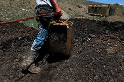 A picture made available on 05 July 2012 of a Mongolian miner carrying a plastic container of coal in a coal mine in the mining town of Nalaikh in Mongolia, 01 July 2012. Once a thriving mining town, Nalaikh is one of first and oldest mining site in Mongolia but has seen a decline in its fortune as mining disasters and accidents plague the site. With little government oversight, only a handful of small companies and informal miners work on the site with scant regard to safety standards. Mongolia is rich in a variety of natural resources including forests, coal, iron ore, gold and copper. Expansion of the mining industry has turned the sector into the most important income source and led to an economic growth rate last year of around 17 per cent. The majority of raw materials are exported to China. Seeking to to reduce the dependency on China for exports and Russian imports, Mongolia has embarked on a policy of closer economic ties with other countries such as Germany, Canada and the United States. Despite impressive growth rates, about one-third of the population lives below the poverty line while unemployment and inflation are high.