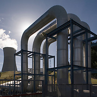 New Zealand, North Island, Ohaaki, Cooling tower and massive steam lines lead to Ohaaki Geothermal Power Station on summer afternoon south of Rotorua