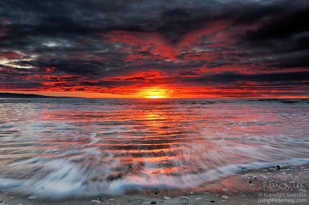 Water racing over ripples on the beach at New Zealand's Molyneux Bay catch some of the fiery color of the sunrise. This beach is located on the south island of New Zealand near Kaka Point in the Catlins.