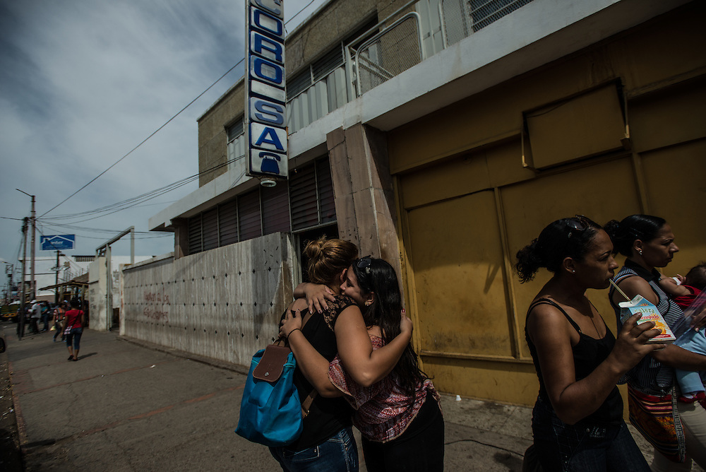 LA VELA, VENEZUELA - SEPTEMBER 23, 2016: Irene Poza hugs her sister goodbye before leaving with men who will smuggle her to Curaçao from Venezuela.  Ms. Poza used to work as a secretary for PDVSA, the state oil company - but lost her job when oil prices fell and the Venezuelan economy started to spiral out of control. Her family's situation is so bad, they struggle to buy enough to eat, and her mother has a heart condition and the family struggles to find the medicines that she needs.  So Irene decided to pay smugglers to take her to Curaçao where she will work cleaning a fast food restaurant and a nightclub. Her situation makes her very angry. She studied hard, and did everything young people are supposed to do to get a good job, she said. In Curaçao she can make in one day cleaning as much money as she would make all month working in a PDVSA office.  She had to stay in this motel because she had to lie to her parents and tell them she was staying with a friend - she said if her mother knew what she was doing, she was afraid the stress would make her heart condition worse. PHOTO: Meridith Kohut for The New York Times