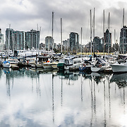 Downtown Vancouver skyline, Vancouver Rowing Club and sailboat masts reflect in Coal Harbour, in British Columbia, Canada. This panorama was stitched from 5 overlapping images.