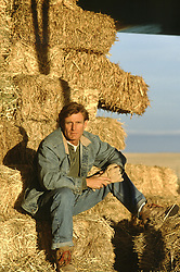 handsome rugged man sitting on hay on a ranch