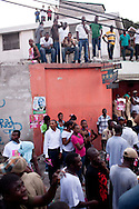 Crowds watch as Haitian presidential candidate Michel Martelly parades through the streets of the Delmas neighborhood after calling for voting results to be canceled in presidential elections on November 28, 2010 in Port-au-Prince, Haiti.