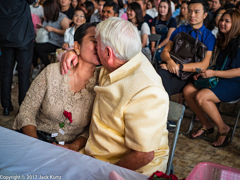 "14 FEBRUARY 2017 - BANGKOK, THAILAND: A couple kisses after getting married in the Bang Rak district in Bangkok. Bang Rak is a popular neighborhood for weddings in Bangkok because it translates as ""Village of Love."" (Bang translates as village, Rak translates as love.) Hundreds of couples get married in the district on Valentine's Day, which, despite its Catholic origins, is widely celebrated in Thailand.      PHOTO BY JACK KURTZ"