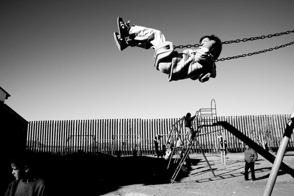 Children play on the playground of the Ignacio Zaragoza Primary School in Palomas, Chihuahua, Mexico, on Tuesday, Jan. 29, 2008. Behind them is the new fence marking the border with the United States.