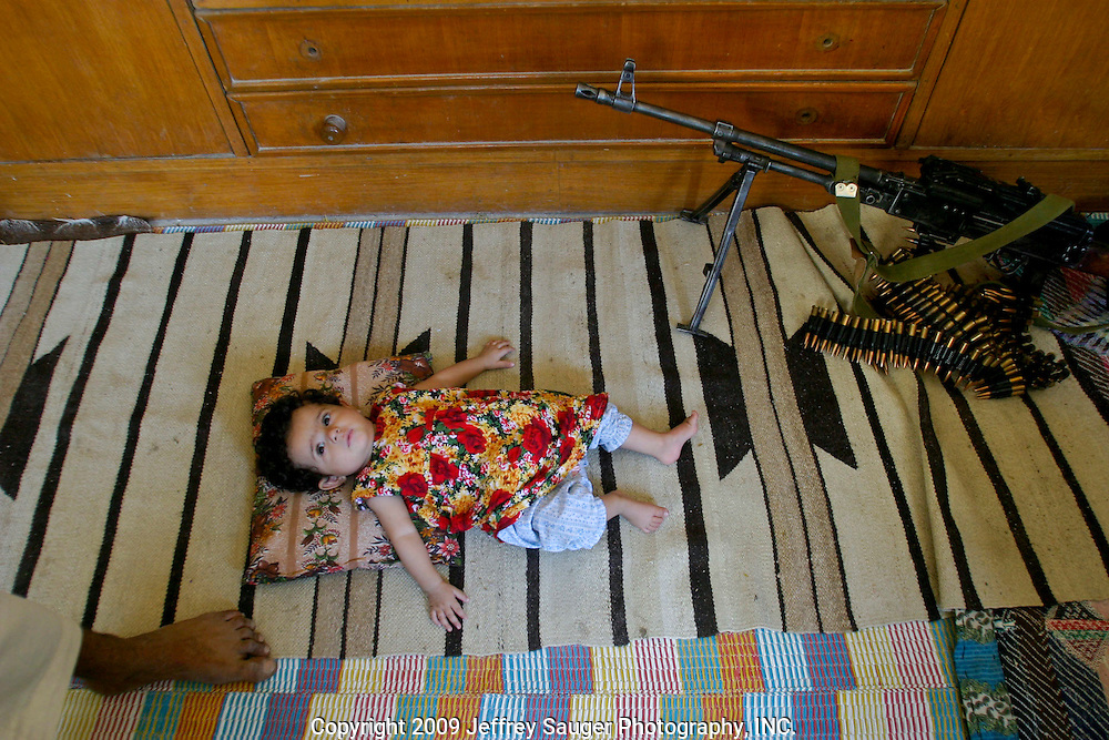 Ali Al-kasid baby lays on the floor near his Russian-made BKC machine gun during the Istikbal, or homecoming celebration, held in honor of his uncle Malik Al-Kasid's family Wednesday, July 30, 2003. The celebration lasts three days with tribal chiefs, family and friends coming and going each day. ..The Al-Kasid family fled Iraq after the Gulf War and their part in the uprising against Saddam Hussein in 1991, spent 3 years in Rafa, Saudi Arabia and finally settled in Dearborn, MI. The family hasn't been home to Iraq in 13 years. After their participation in the 1991 uprising, Saddam Hussein's forces burned the Al-Kasid family Motheff, along with their cars, to the ground.