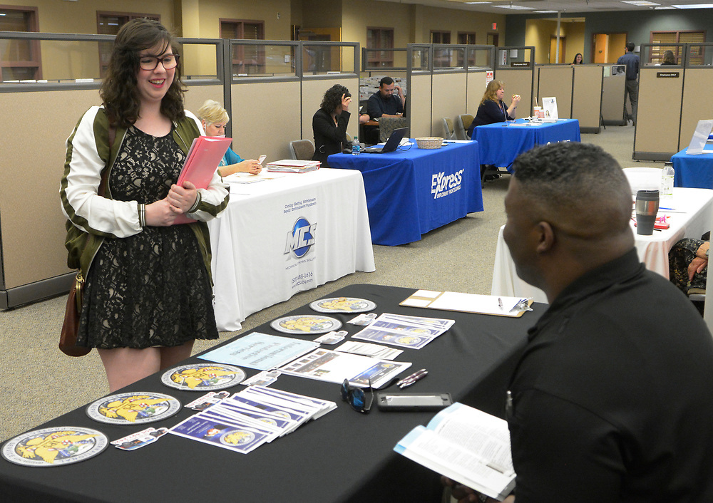 gbs041717a/BUSINESS -- Kelli Hammond of Albuquerque talks with Exevius Seals with International Protection Service at a job fair at the New Mexico Workforce Connection on Monday, April 17, 2017. (Greg Sorber/Albuquerque Journal)