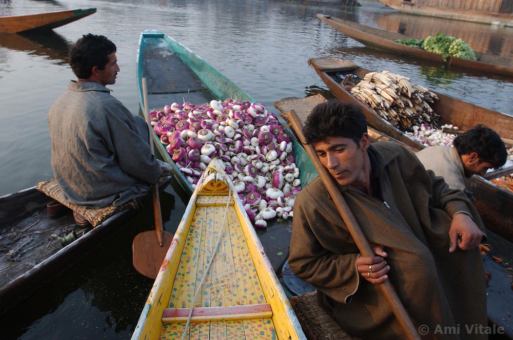 Kashmiri men sell their vegetables at a floating market in the early hours before sunrise on Dal Lake in the troubled summer capital of Kashmir, Srinagar India, November 24, 2001. In the background, echoing through the nearby mountains, gunshots and fighting could be heard. Kashmir was once a tourist hotspot but now vendors struggle to survive in a place that has seen nearly 1000 civilians killed this year alone and 1,765 wounded in a brutal conflict that the United Nations calls the most dangerous place in the world.  (Photo by Ami Vitale/Getty Images)