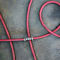 Africa, Zambia, Livingstone, Details of coiled air hose on concrete floor inside Foley's Land Rover garage near Victoria Falls
