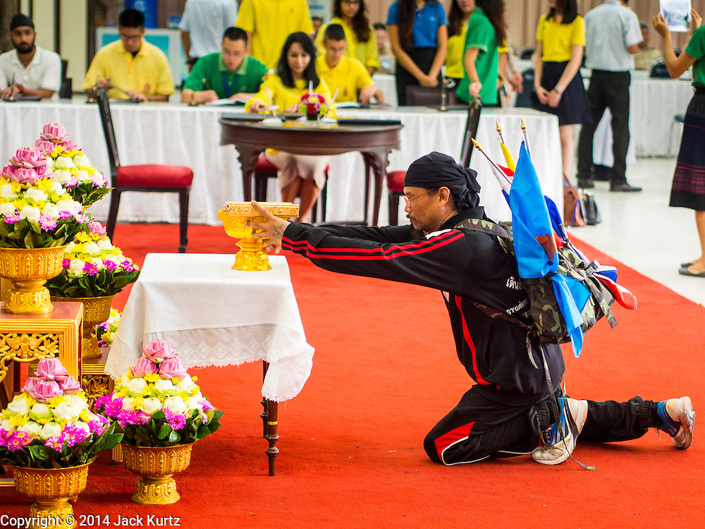 28 NOVEMBER 2014 - BANGKOK, THAILAND:  A man who said he walked all the way to Bangkok from Nakhon Ratchisma (Korat), about 235 kilometers, makes an offering after praying for Bhumibol Adulyadej, the King of Thailand, in the lobby of Siriraj Hospital. The King was born on December 5, 1927, in Cambridge, Massachusetts. The family was in the United States because his father, Prince Mahidol, was studying Public Health at Harvard University. He has reigned since 1946 and is the world's currently reigning longest serving monarch and the longest serving monarch in Thai history. Bhumibol, who is in poor health, is revered by the Thai people. His birthday is a national holiday and is also celebrated as Father's Day. He is currently hospitalized in Siriraj Hospital, recovering from a series of health setbacks. Thousands of people come to the hospital every day to sign get well cards for the King.      PHOTO BY JACK KURTZ