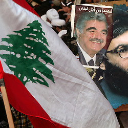 A protester holds a photo of slain former Lebanese Prime Minister Rafik Hariri and Hezbollah chief Sheikh Hassan Nasrallah, Beirut, Lebanon, March 8, 2005. Hundreds of thousands of pro-Syrian protesters gather and chant anti-American slogans. Hezbollah, the militant Shiite Muslim group, called for a nationwide demonstration against foreign intervention and to counter weeks of massive anti-Syrian rallies.